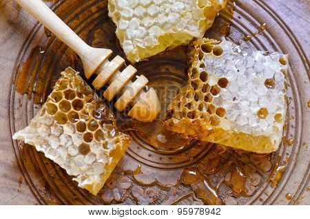 Honeycomb With Honey Dipper On Vintage Wooden Plate