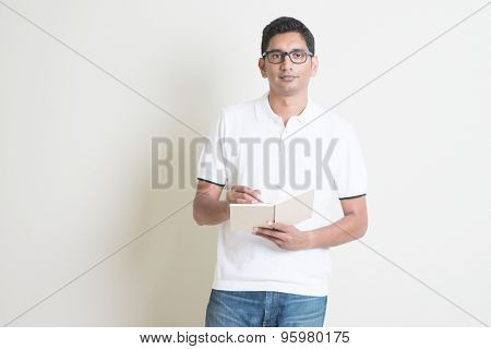 Portrait of Indian guy taking note on booklet. Asian man standing on plain background with shadow and copy space.