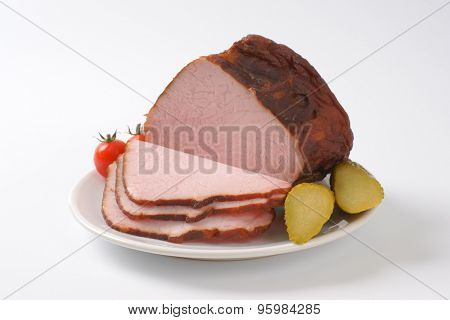 sliced chunk of roasted pork on white plate