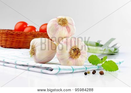 close up of fresh garlic bulbs on checkered dishtowel