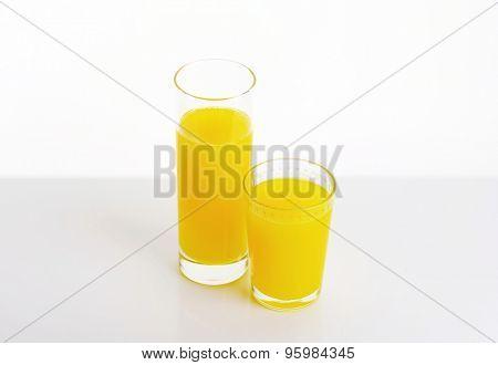 two glasses of orange juice on white background