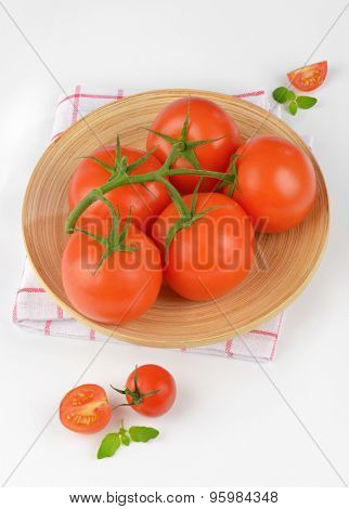 fresh tomatoes on bamboo plate and checkered dishtowel