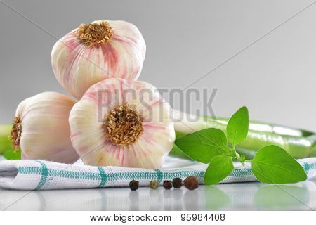 detail of fresh garlic bulbs on checkered dishtowel