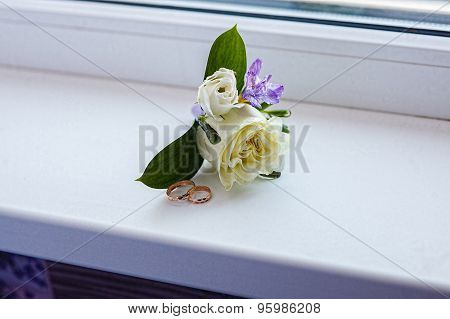 Wedding rings and flower boutonniere on the sill of a window is