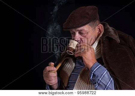 Man being chilled to the bone drinks coffee and smokes tobacco-pipe in the darkness