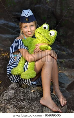 The girl in the marine cap with a toy frog