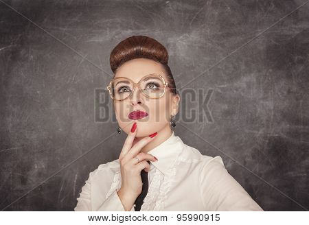 Teacher Woman Looking Up Above On The Blackboard Background