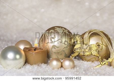Festive classical christmas decoration in white and gold with horse and one burning candle for the first advent.