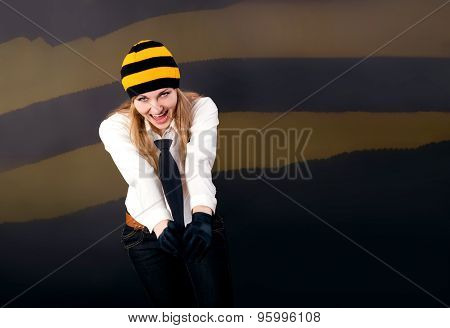 Beautiful and happy blonde yells something in a cap holding tie