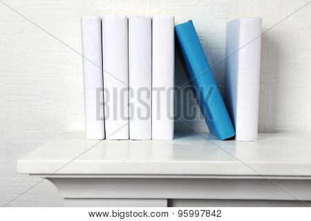 Blank books and one blue on shelf on white wallpaper background