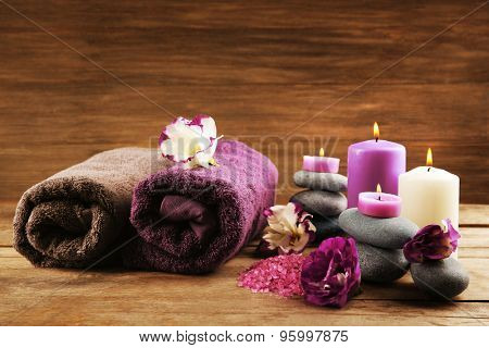 Spa still life with towels, purple flowers and candlelight on wooden background
