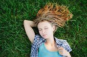foto of dreadlock  - Stylish slim girl with dreadlocks lying on green grass - JPG