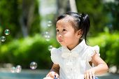 pic of blowers  - Adorable girl playing bubble blower at outdoor - JPG