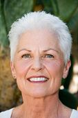 stock photo of 55-60 years old  - head shot of a beautiful 55 to 60 year old caucasian woman in an outdoor setting - JPG