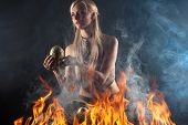stock photo of woman dragon  - beautiful woman with a nest egg dragons in the fire isolated on black - JPG