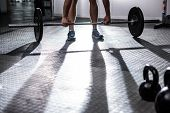 Muscular man lifting a barbell in crossfit gym poster