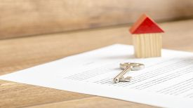 pic of rental agreement  - Silver house key lying on a contract of house sale lease insurance or mortgage in a real estate concept viewed low angle with focus to the tip - JPG
