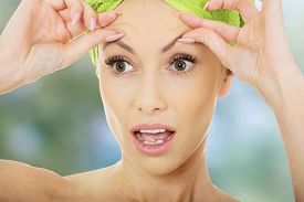 pic of forehead  - Beauty woman checking wrinkles on her forehead - JPG