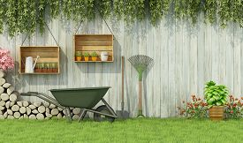 stock photo of wooden fence  - Tools for gardening in a garden with old wooden fence - JPG