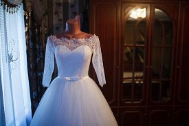 image of dress mannequin  - White wedding dress hanging on a mannequin in a room inside the house - JPG