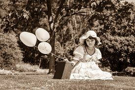 image of disappointed  - Sad and disappointed young girl sitting with her suitcase alone in the garden - JPG