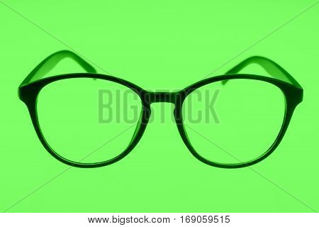 Close up of eyeglasses isolated on green background