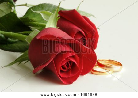 Wedding Rings And Red Roses