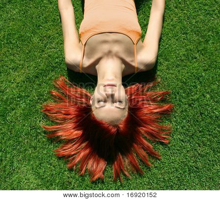 girl with red hair lying on a green grass