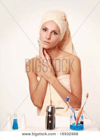 young woman removing make up from her face