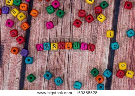 Absolute - Word Created With Colored Wooden Cubes. Stock Photo.