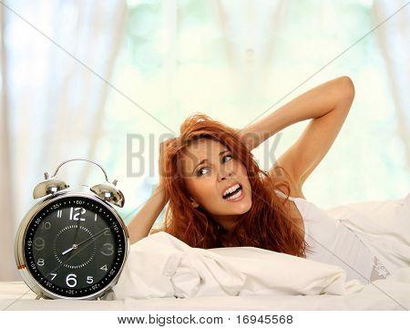 joven tumbado en la cama con reloj despertador
