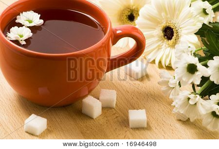 Cup of herbal tea, flowers and cubes of sugar on a wooden board