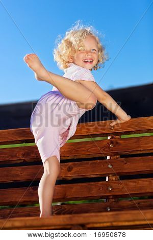 Cute Little Girl With Blond Curly Hair Playing On Wooden Chain Swing