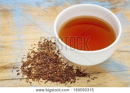 rooibos red tea  -  a white cup of a hot drink and loose leaves on grunge wood background, tea made from the South African red bush, naturally caffeine free