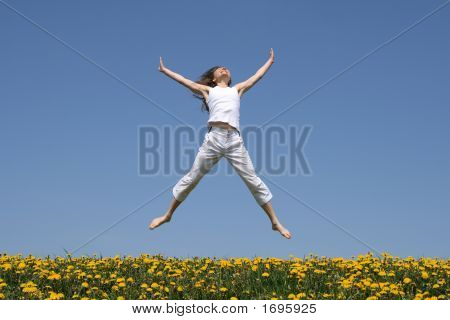 Smiling Girl Jumping In Flowering Meadow