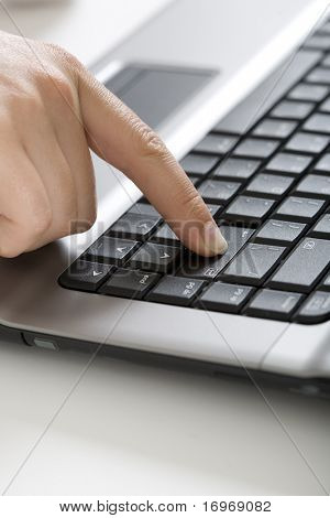 Close-up of human finger pressing  the button - enter