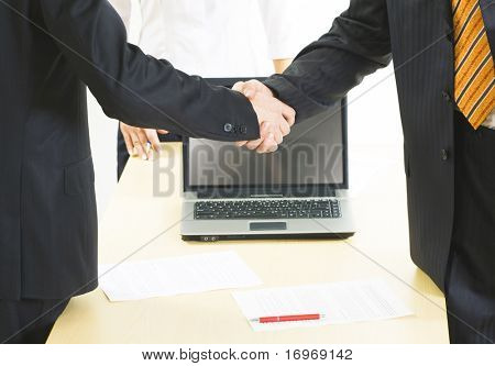 Image of great business handshake over workplace