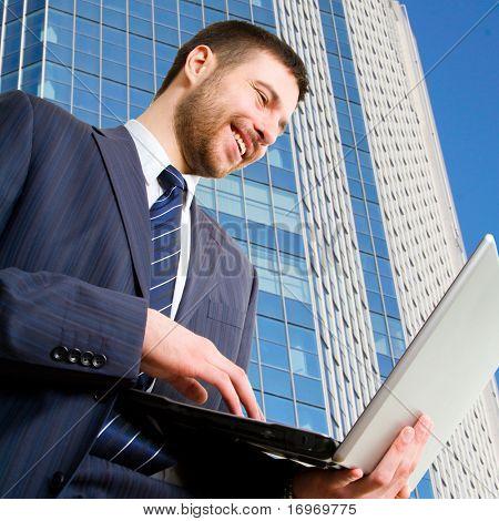 Walking businessman using his lap-top against a  skyscraper