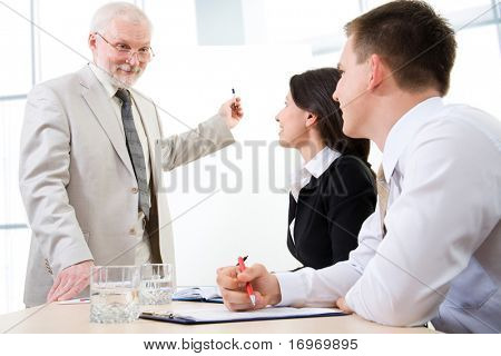 Three business people listening to a  speaker