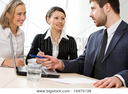 Image of business conversation of three businesspeople