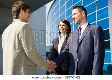 Two businessmen shaking hands and a businesswoman near business centre