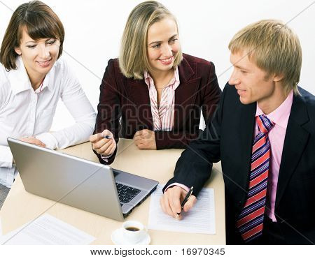 Three working businesspeople sitting at the table