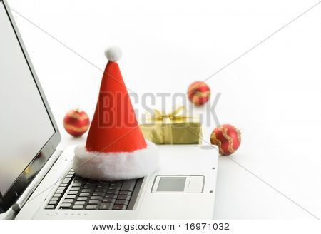 Santa Claus hat and christmas gifts on a workplace