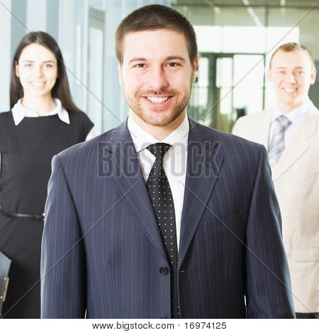 Young businessman looking at camera with smile between his colleagues