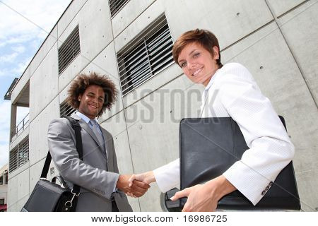 Salespeople shaking hands in front of office building