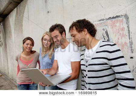 Group of friends standing against wall with laptop computer