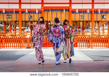 KYOTO, JAPAN - NOVEMBER 10, 2016: Young women wearing traditional japanese kimonos at Fushimi Inari Shrine in Kyoto, Japan. Kimono is a Japanese traditional garment.