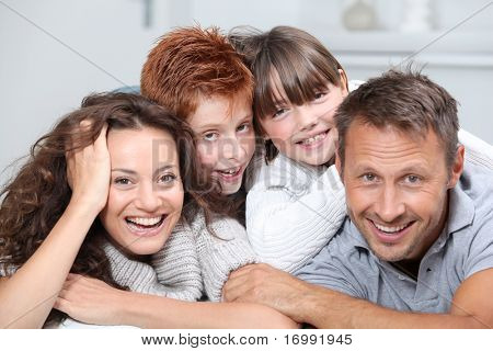 Happy family of 4 people laying on a sofa at home