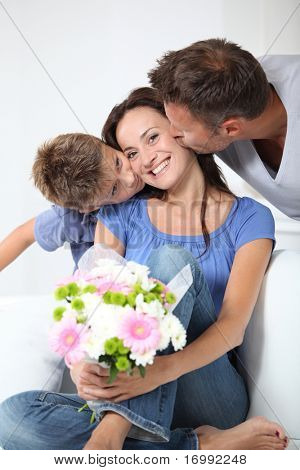 Father and child kissing woman on mother's day