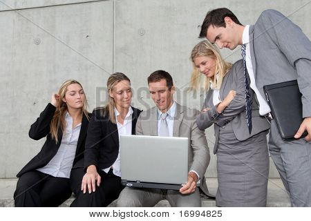 Group of five business people meeting in front of building